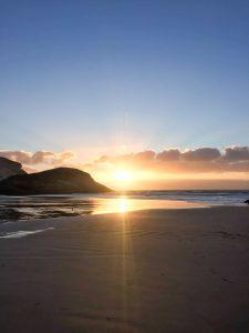 photo of the sun setting at wharariki beach golden bay nz