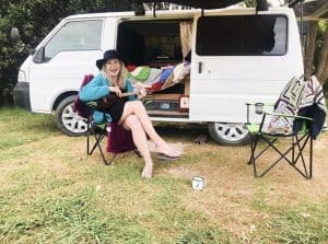 a photo of me sitting in front of my campervan while van living full time for 3 months around New Zealand
