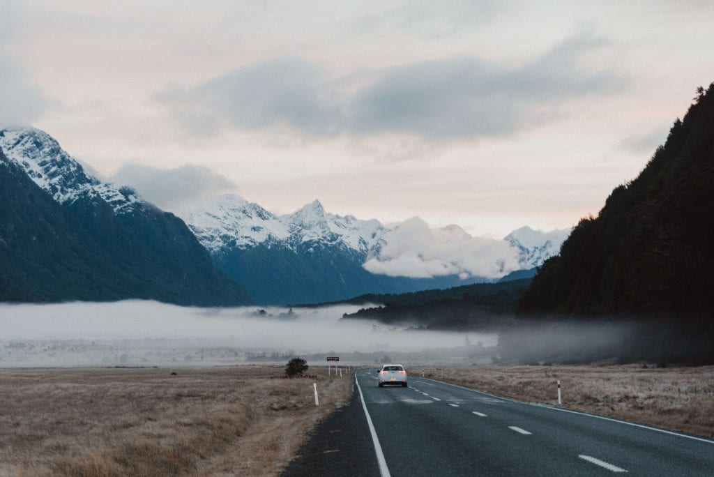 a photo of a car driving the milford road in the southland region