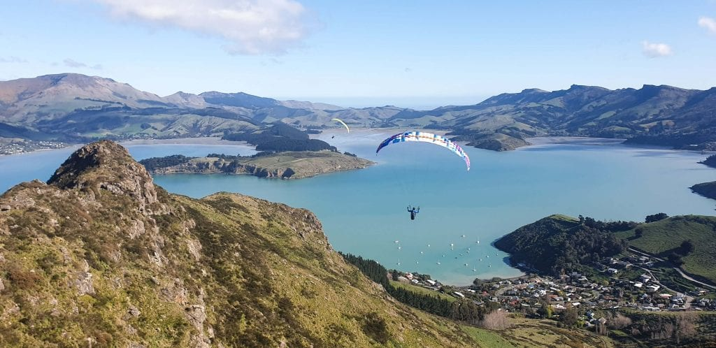 a photo of my friend paragliding above banks peninsula in the canterbury region new zealand