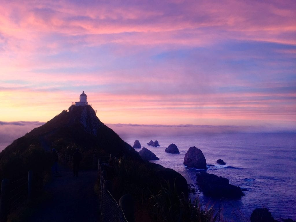 the catlins is one of the best places to travel new zealand in a campervan. This photo is taken at Nugget point at sunrise!